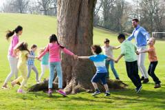 Waldorfkinder tanzen um einen Baum