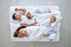 Familie schäft gemeinsam im Bett