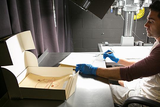 Mitarbeiter der ARL holt vorsichtig Skizzen aus einer kleinen Kiste