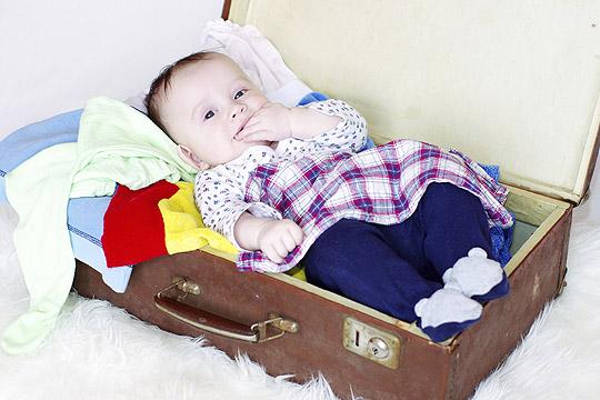 Baby liegt in gepacktem Koffer