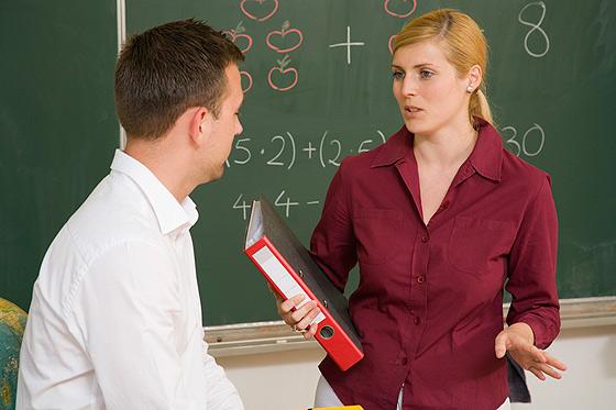 Lehrerin vor Tafel im Gespräch mit Vater bei Elternabend