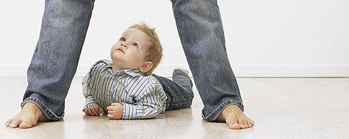 Baby unter Beinen von Elternteil