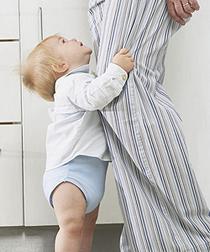 Elterngeld: Kind kalmmert sich an das Bein seiner Mutter.