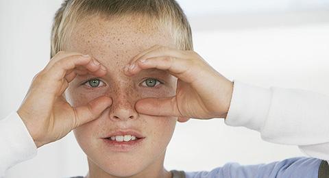 Junge bildet Brille mit seinen Händen