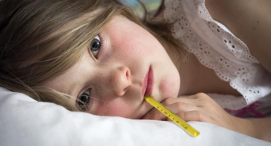 Mädchen liegt mit Fieber im Bett