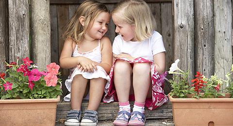 Zwei Mädchen sitzen nebeneinander