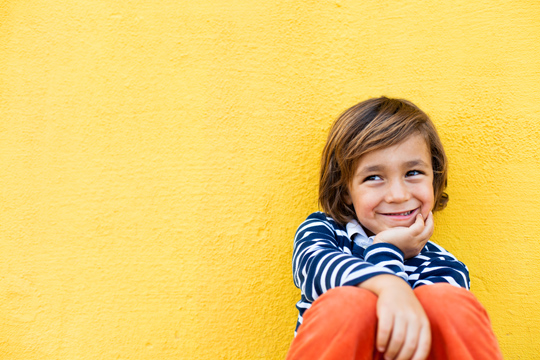 Kind vor gelber Wand
