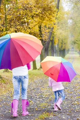 Mutter und Tochter unter bunten Regenschirmen