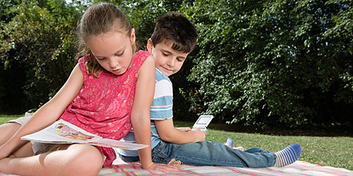 Mädchen mit Zeitschrift und Junge mit Handspielgerät auf Wiese