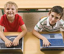 Zwei Jungen sitzen vor Laptops