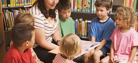 Kindergärtnerin liest Kinder etwas vor