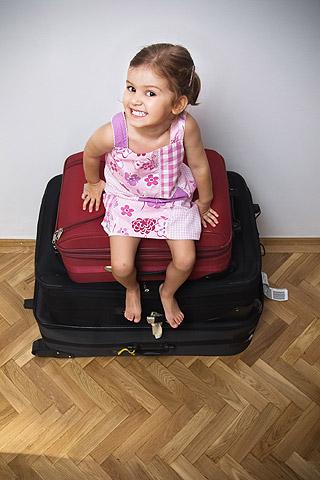 Mädchen sitzt ungeduldig auf gepackten Koffern