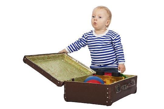 Kleiner Junge packt Spielzeug in einen Koffer