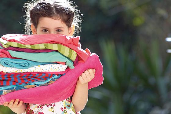 Second Hand für Kinder: Mädchen mit einemn Stapel Klamotten