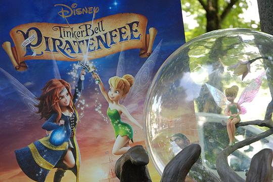 """Tinkerbell vor dem Filmplakat zu """"Tinkerbell und die Piratenfee"""""""