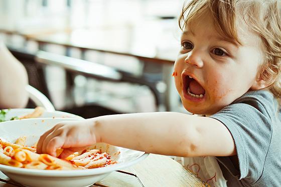 Baby matscht mit Nudeln