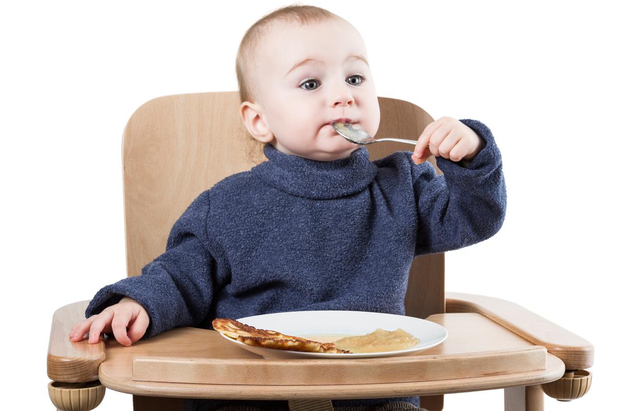 Baby isst Pfannkuchen mit Apfelmus