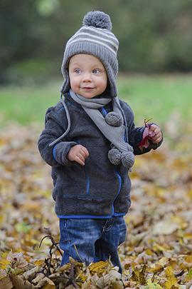 Kleinkind spielt im Laub
