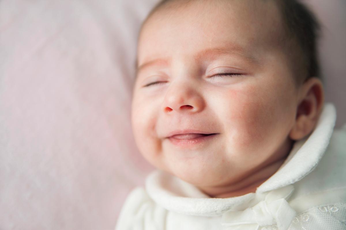 Baby träumt und lacht im Schlaf
