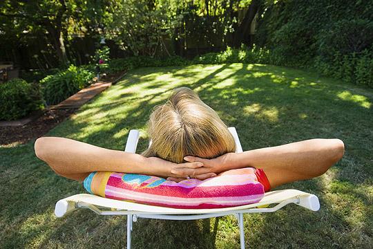 Frau entspannt auf einer Liege im Garten