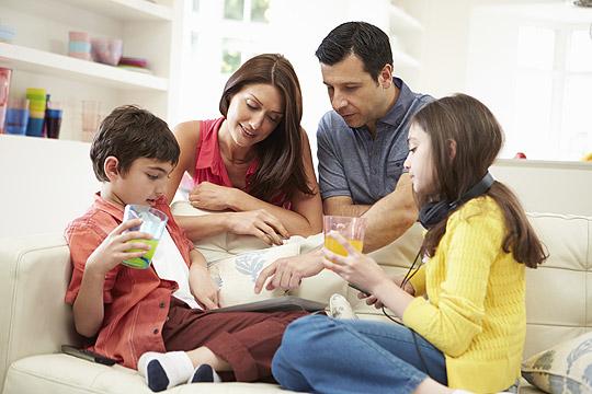Familie sittz auf der Couch und plant den Urlaub auf Balkonien
