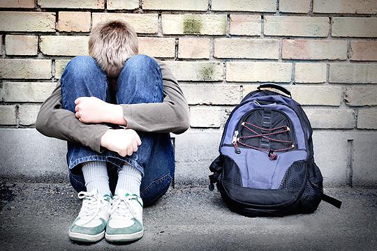 trauriger Junge lehnt an Wand