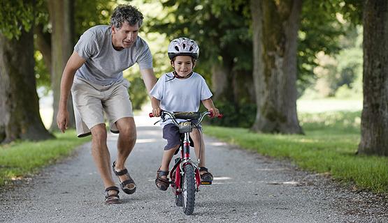 Fahrrad fahren lernen: Vater hilft Sohn