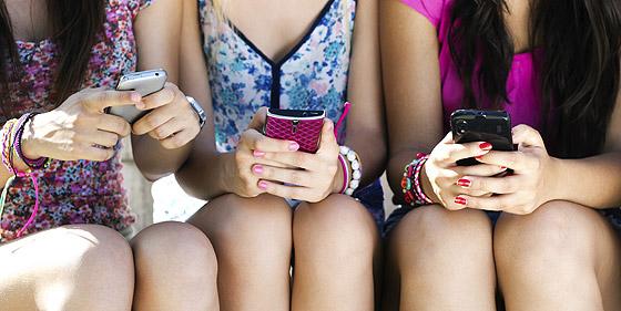 Internetsucht: drei Mädchen mit ihrem Smartphone
