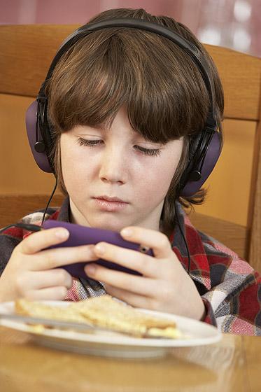 Internetsucht: Junge surft am Esstisch mit dem Smartphone