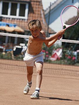 Junge schlägt nach dem Tennisball