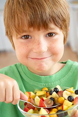 Junge isst Obstsalat