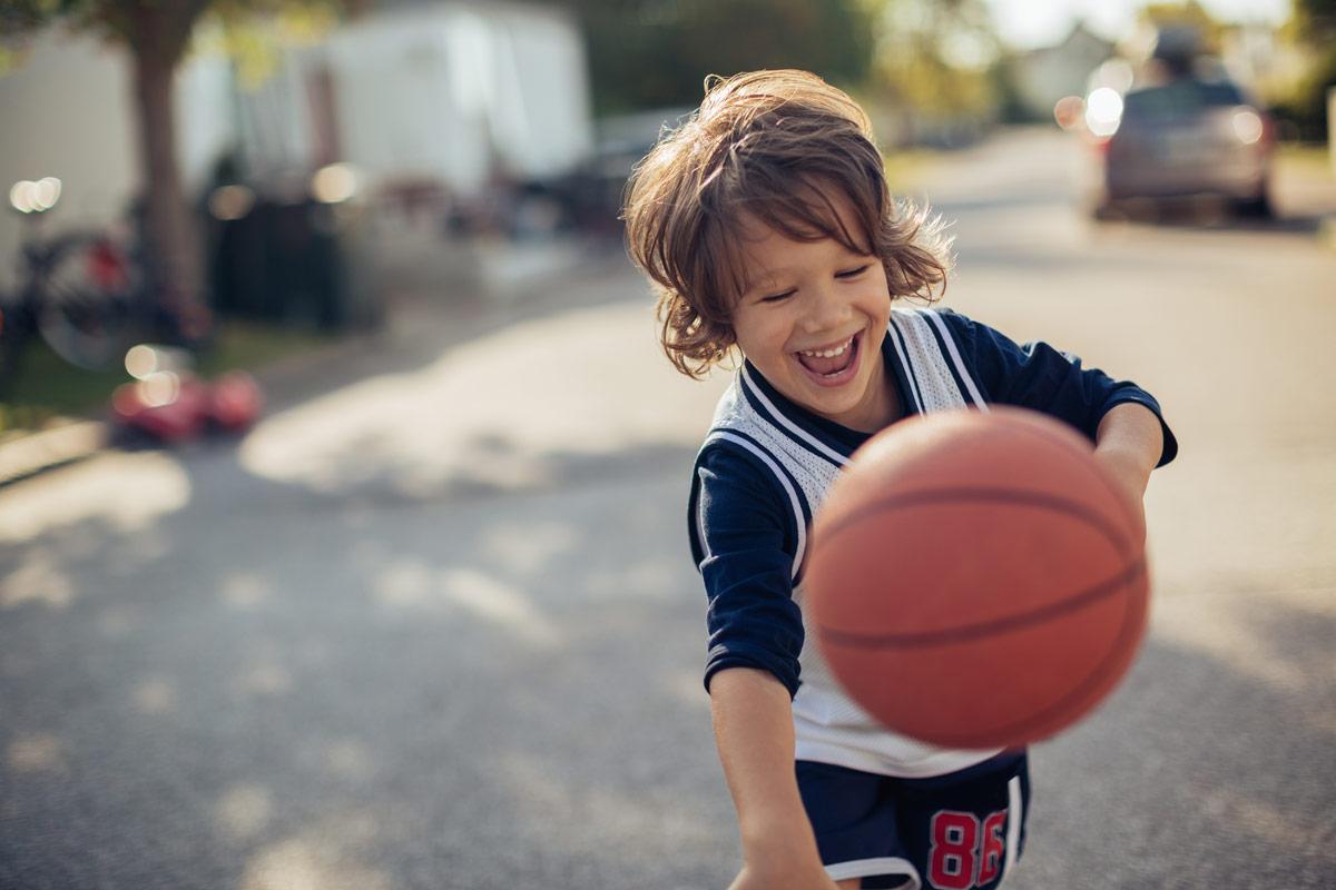 Junge spielt Baskettball auf der Straße
