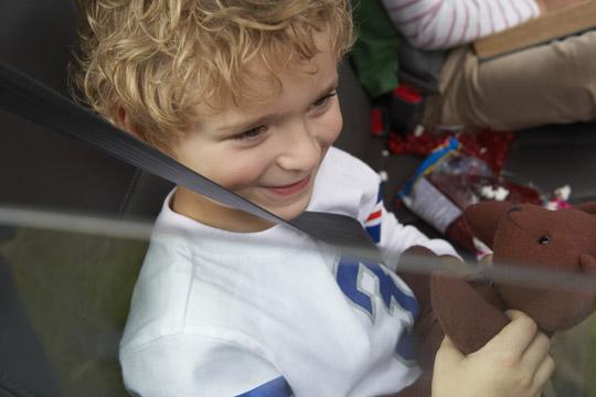 Junge sitzt mit Lieblingsspielzeug im Auto
