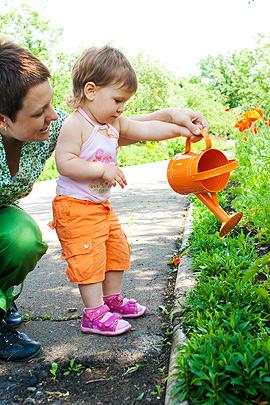 Kleinkind und Mutter gießen Blumen