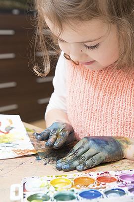 Kleines Mädchen mal mit einem Farbkasten