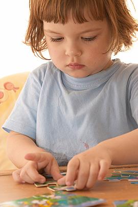 Kleines Mädchen spielt mit einem Puzzle