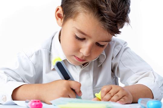 Junge markiert in einem Lehrbuch