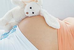 Plüschhase liegt auf Babybauch einer Schwangeren