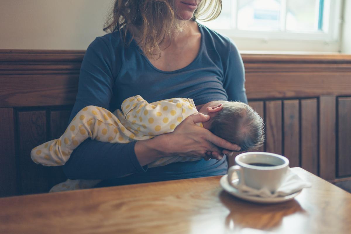 Mutter stillt Baby im Cafè