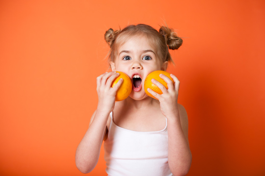 Kind vor oranger Wand