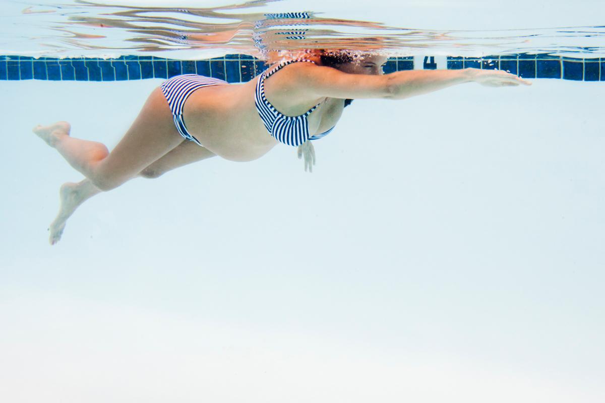 Schwangere Frau schwimmt im Wasser
