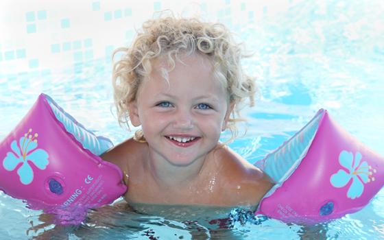 Schwimmhilfen: Mädchen mit Schwimmfkügeln im Pool