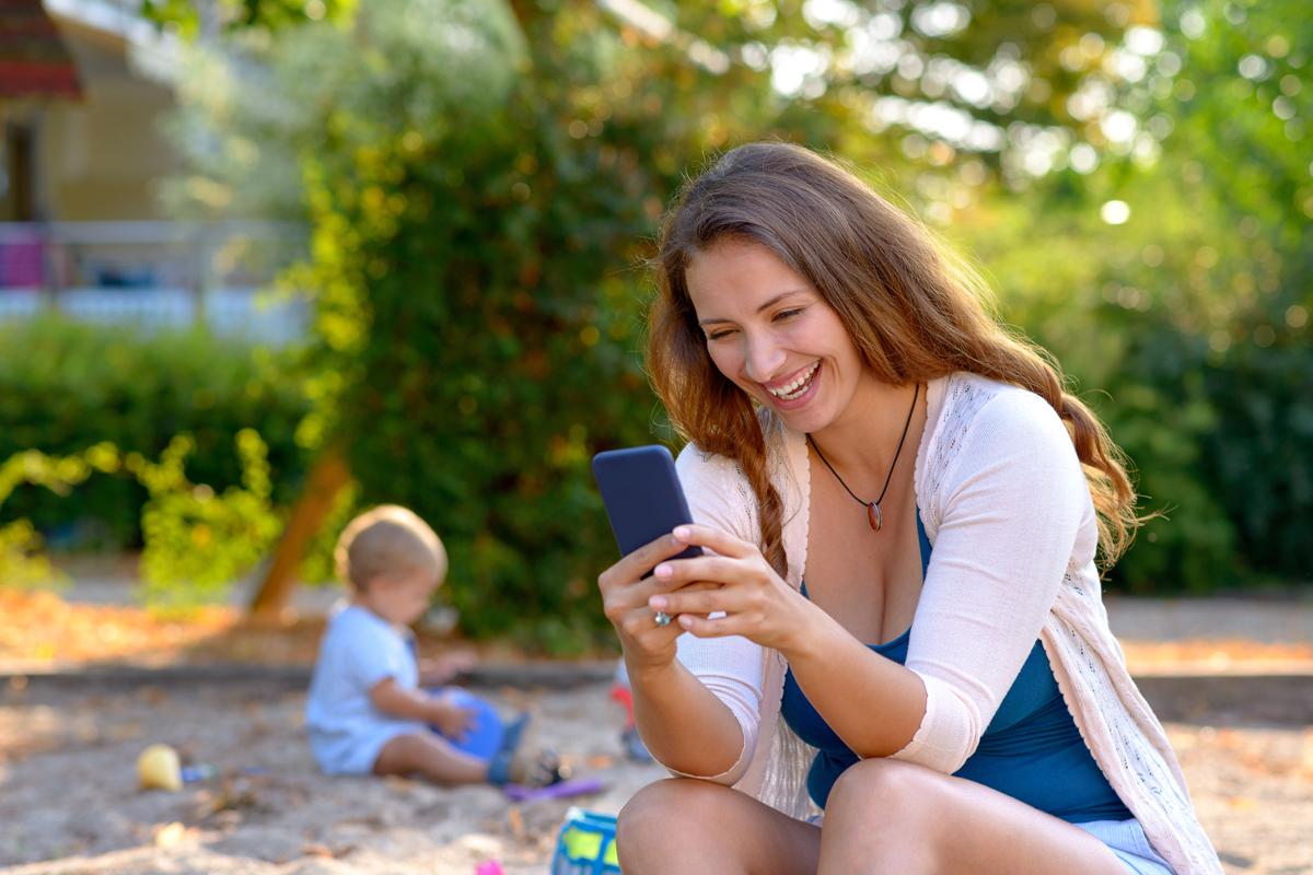 Mutter mit Smartphone auf dem Spielplatz