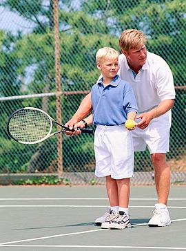 Tennislehrer trainiert kleinen Jungen