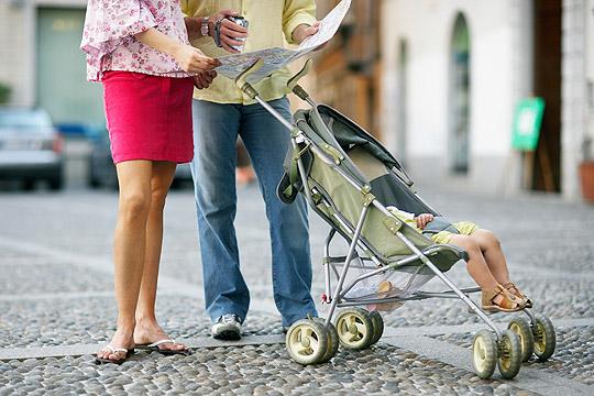 Vater, Mutter und Baby im Buggy im Urlaub