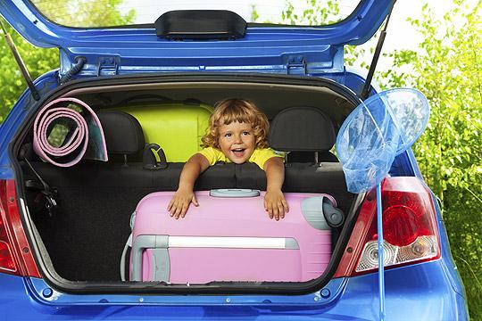 Kind sitzt zwischen Koffern im Kofferraum