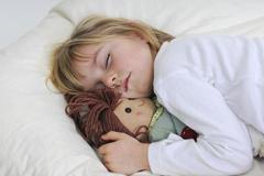 Kind schläft mit Kuscheltier