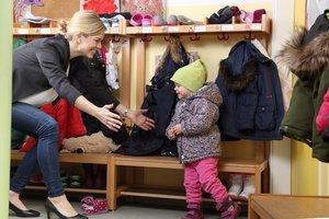 Mutter nimmt Kind im Kindergarten in die Arme
