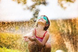 Hitzefrei: Ein Mädchen erfrischt sich mit Wasser