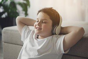 Junge sitzt entspannt mit Kopfhörern.